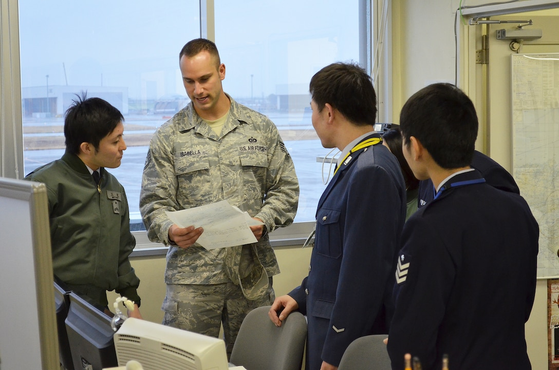 Staff Sgt. Anthony Isabella, 374th Operations Support Squadron Non-Commissioned Officer in charge of airfield management training, discusses aspects of the Airfield Management mission with his Japanese Air Self Defense Force counterparts as part of a bilateral exchange program at Komaki Air Base, Japan, March 5, 2014.  Eight NCO's from Yokota traveled to Komaki to see how their JASDF counterparts conducted their mission and to learn more about Japanese culture as part of the exchange. (U.S. Air Force photo by Tech. Sgt. Christopher Marasky/Released)