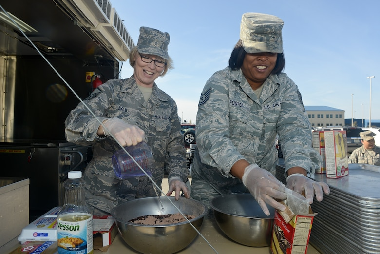 U.S. Air Force Master Sgt. Elisa Lyle, left, and Tech. Sgt. Jocelyn Foster, 116th Force Support Squadron, Services Flight (FSS/FSV), Georgia Air National Guard, Robins Air Force Base, Ga., mix ingredients in preparation for baking a cake in a Deployable Ready Mobile Kitchen Trailer (DRMKT) while training with the 136th FSS/FSV, Texas Air National Guard, at Naval Air Station Fort Worth Joint Reserve Base, Texas, Feb. 22, 2014. Members of the 116th FSS/FSV participated in the two-day training event in anticipation of receiving their own DRMKT in July 2014. (U.S. Air National Guard photos by Master Sgt. Charles Hatton/Released)
