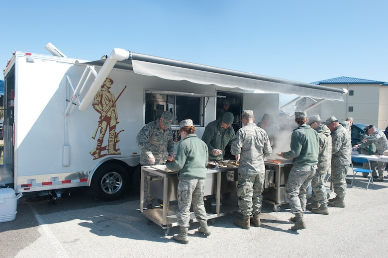 Members of the 136th Force Support Squadron, Services Flight (FSS/FSV), Texas Air National Guard, serve hot meals to Guardsmen during a unit training assembly while demonstrating the functionality of a newly assigned Deployable Ready Mobile Kitchen Trailer (DRMKT) to members of the 116th Force Support Squadron, Services Flight, Georgia Air National Guard, Robins Air Force Base, at Naval Air Station Fort Worth Joint Reserve Base, Texas, Feb. 23, 2014. Members of the 116th FSS/FSV participated in a two-day training event in anticipation of receiving their own DRMKT in July 2014. (U.S. Air National Guard photos by Master Sgt. Charles Hatton/Released)