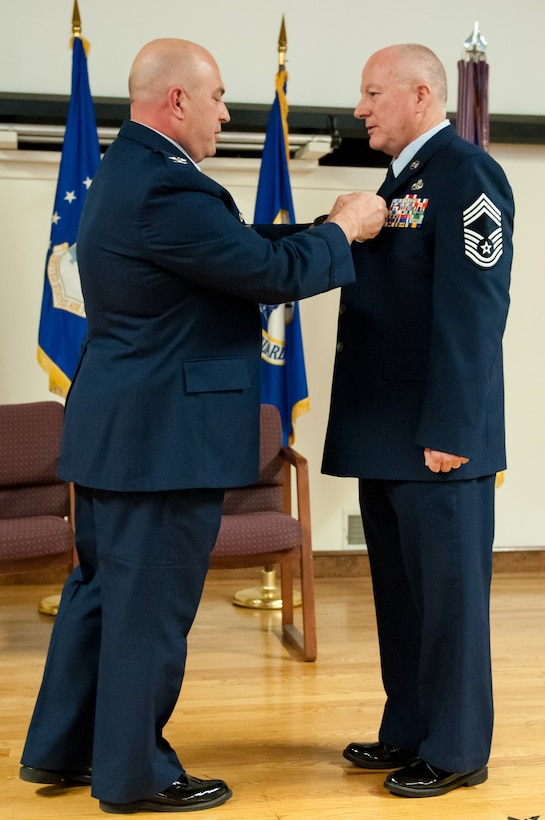 Col. Kenneth Dale (left), commander of the 123rd Maintenance Group, pins the Meritorious Service Medal to the jacket of Chief Master Sgt. Jim Amburgey during Amburgey's retirement ceremony at the Kentucky Air National Guard Base in Louisville, Ky., on Jan. 12, 2014. Amburgey served for more than 38 years. (U.S. Air National Guard photo by Staff Sgt. Vicky Spesard)