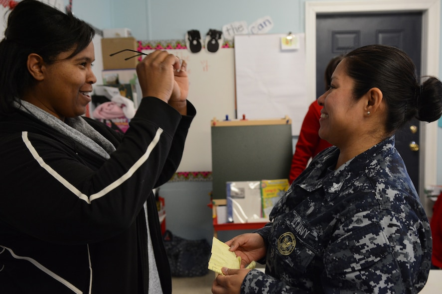 Hospital Corpsman 2nd Class Ana Chacon, Operational Health Support Group San Diego optometry technician, gives a pair of glasses to one of the Lighthouse Christian Academy teachers during Cajun Care 2014 in Abbeville, La., March 6, 2014. Air National Guard and Navy personnel visited the school to examine the students' and teachers' eyes, and later returned with glasses for all who needed them. (Air National Guard photo by Senior Airman Andrea F. Liechti)