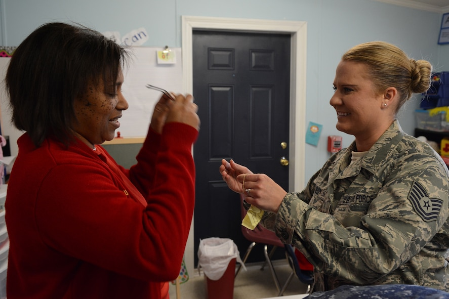 Tech. Sgt. Michelle Reed, 153rd Medical Group optometry technician, gives a pair of glasses to one of the Lighthouse Christian Academy teachers during Cajun Care 2014 in Abbeville, La., March 6, 2014. Air National Guard and Navy personnel visited the school to examine the students' and teachers' eyes, and later returned with glasses for all who needed them. (Air National Guard photo by Senior Airman Andrea F. Liechti)