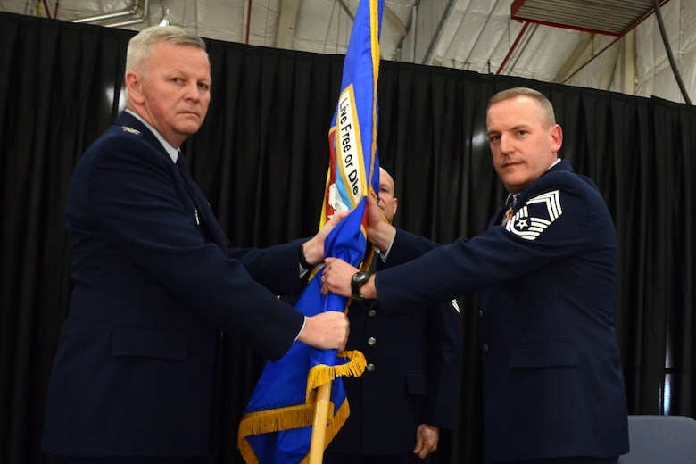 PEASE AIR NATIONAL GUARD BASE, N.H. -- 157th Air Refueling Wing Commander Col. Paul Hutchinson passes the wing flag to Chief Master Sgt. Jamie Lawrence upon appointment as the new wing command chief. Lawrence replaces Chief Master Sgt. Brenda Blonigen who served in the position for more than five years. Lawrence's previous role was as the 66th Force Support Squadron superintendent. (N.H. National Guard photo by Tech. Sgt. Mark Wyatt/RELEASED)