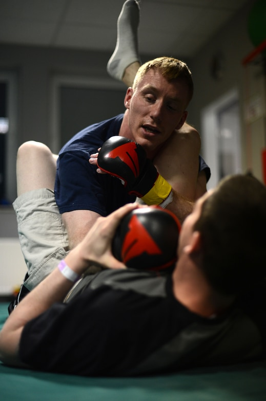 U.S. Air Force Senior Airman Sean Whitaker, a Spangdahlem mixed martial arts member from Pittsburgh, practices grappling techniques on a teammate before a fight at an MMA tournament in Pruem, Germany, March 8, 2014. Tournament participants practice fighting techniques before a fight to ensure they are ready to take on their opponent. (U.S. Air Force photo by Senior Airman Gustavo Castillo/Released)