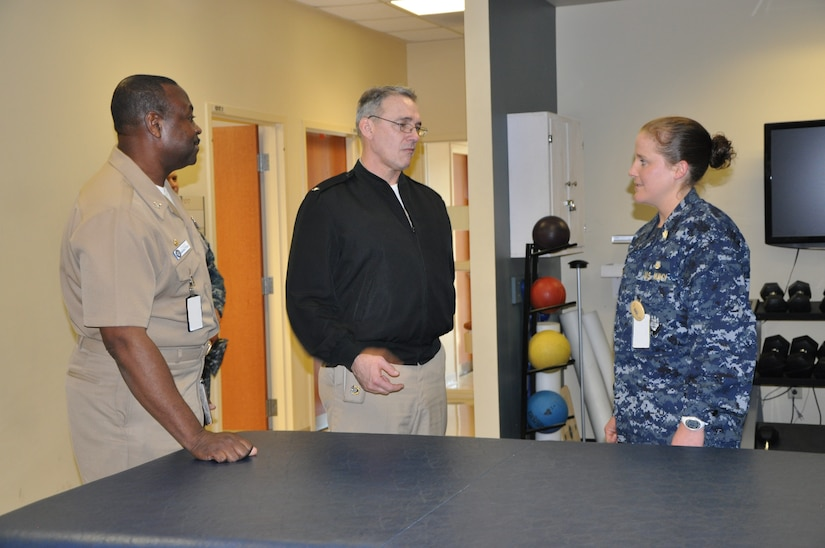 Navy Rear Adm. Rick Williamson, Commander of Navy Region Southeast, discusses physical therapy techniques and methods with Navy Lt. Lauren Brown, Naval Health Clinic Charleston physical therapist, during a visit to the clinic Tuesday. NHCC's Commanding Officer Capt. Marvin Jones, left, gave Williamson a tour of NHCC, which provides a wide range of primary, specialty, ancillary and occupational health services for service members, family members and veterans of Joint Base Charleston - Weapons Station. (Photo by Petty Officer 3rd Class Caralyn Mulyk, NHCC Public Affairs)
