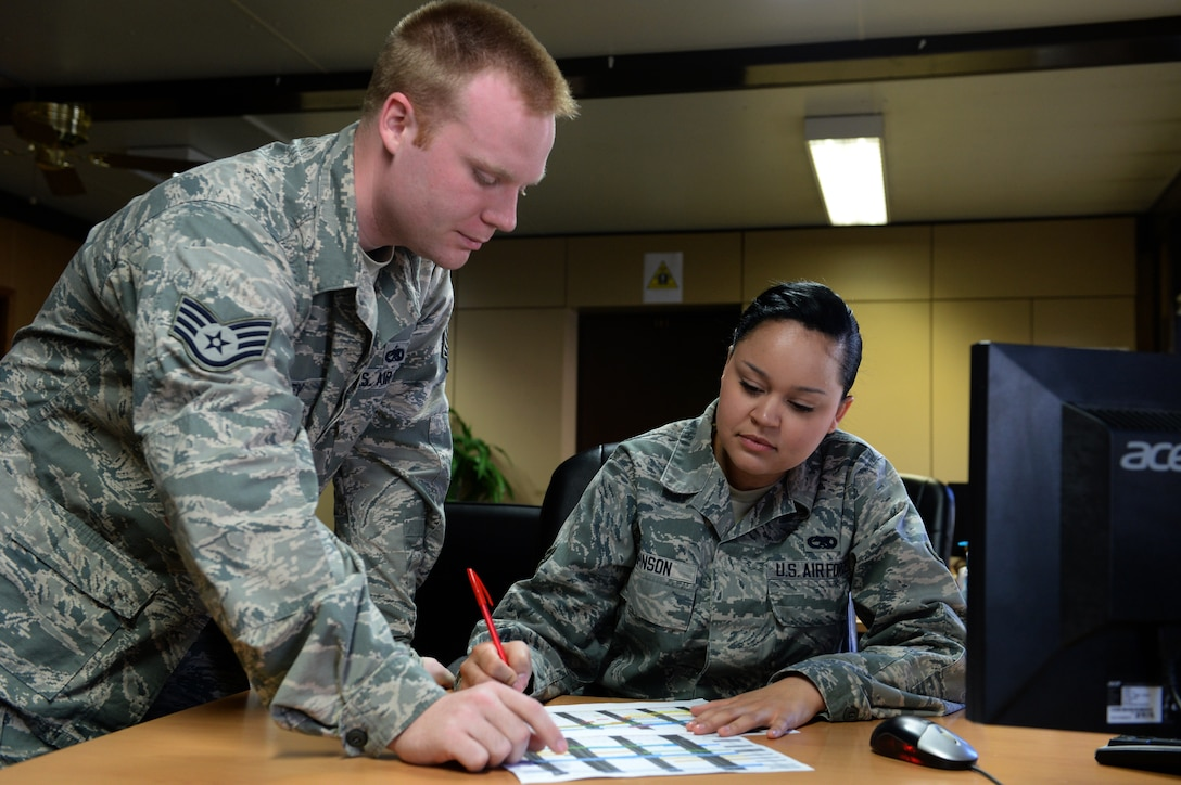 U.S. Air Force Staff Sgt. David Hartley and Airman 1st Class Chalayna Johnson, 52nd Maintenance Group maintenance operators, review the monthly flying schedule at Spangdahlem Air Base, Germany, March 10, 2014. Maintenance operations accomplishes their mission with a team of more than 100 people, from 16 different jobs, in eight sections. (U.S. Air Force photo by Senior Airman Alexis Siekert/Released)