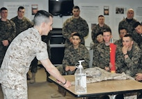 Marine Staff Sgt. Christopher Kirby, marshal arts instructor trainer and Chemical, Biological, Radiological and Nuclear defense instructor, teaches Marines Awaiting Training how to properly roll up the sleeves of their summer uniforms. Marines went sleeves-up Sunday, after a more than two-year-old sleeves- down policy was rescinded by the commandant of the Marine Corps. The bottle is for securing the uniform while rolling up the sleeve.