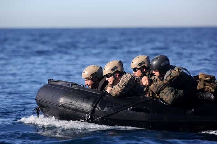 Marines with Bravo Company, 1st Reconnaissance Battalion, prepare to board the USS Freedom from a zodiac during on and off loading drills three miles off the coast of Del Mar beach Marine Corps Base Camp Pendleton, Calif., March 10, 2014. The purpose of the training was to find out if the Marines could launch and recover a zodiac, a small inflatable boat with a hand steered engine, onto a littoral combat ship. They discovered that using the LCS gave them the ability to insert and recover reconnaissance teams from a greater distance out at sea.