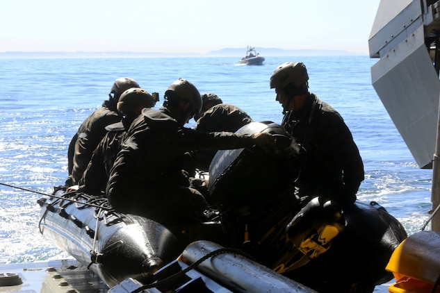 Marines with Bravo Company, 1st Reconnaissance Battalion, prepare to launch a zodiac from the USS Freedom during on and off loading drills three miles off the coast of Del Mar beach Marine Corps Base Camp Pendleton, Calif., March 10, 2014. The purpose of the training was to find out if the Marines could launch and recover a zodiac, a small inflatable boat with a hand steered engine, onto a littoral combat ship. They discovered that using the LCS gave them the ability to insert and recover reconnaissance teams from a greater distance out at sea.