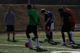 The Quantico Middle/High School boys soccer team practices ball handling skills during practice on March 11, 2014, at Butler Stadium. The team veterans are working to train the new players in the fundamentals while inspiring a love for the game.