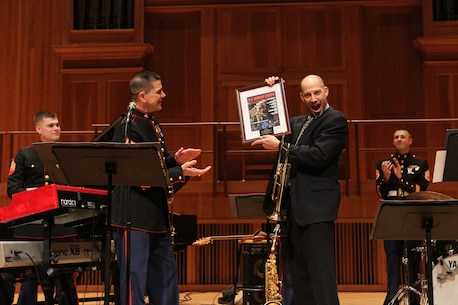 NEW YORK - Michael Mossman, director of music at Queens College, is presented a picture signed by the members of the Marine Corps Jazz Ensemble on March 5 at Queens College's Aaron Copland School of Music.  The Marine Corps Jazz Ensemble is touring the 1st Marine Corps District's area of operations to spread knowledge of the Marine Corps' Musician Enlistment Option Program.  (U.S. Marine Corps photo by Lance Cpl. Brandon Thomas).