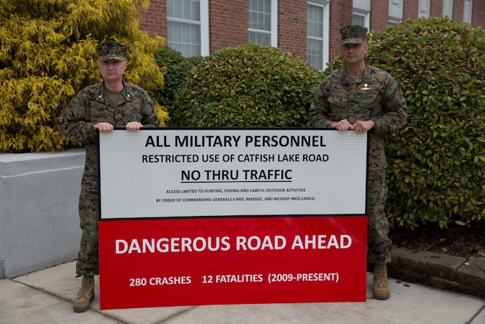 Col. James W. Clark, deputy commander of Marine Corps Installations East, and Sgt. Maj. Ernest K. Hoopii, Marine Corps Installations East sergeant major, display the new Catfish Lake Road warning sign aboard Marine Corps Base Camp Lejeune, March 6. It was deemed off-limits to base personnel due to the dangerous driving conditions.