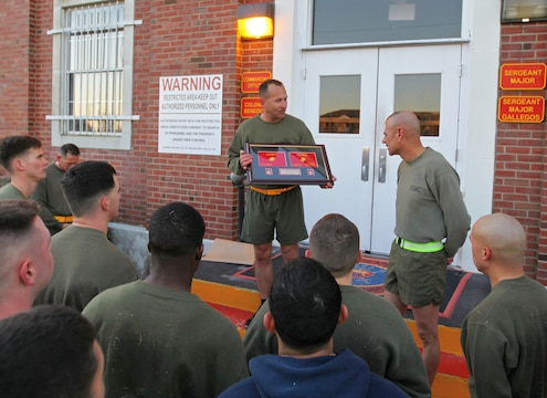 Col. Scott F. Benedict, center, the commanding officer of the 24th Marine Expeditionary Unit, delivers a unit gift to Sgt. Maj. Octaviano Gallegos Jr., the 24th Marine Expeditionary Unit sergeant major, March 14, 2014, after a unit physical training event at Camp Lejeune, N.C. Gallegos' relinquished duties as 24th MEU sergeant major later in the day to Sgt. Maj. Lanette N. Wright, who will be the first female MEU sergeant major.