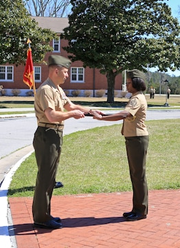 Col. Scott F. Benedict, the commanding officer of the 24th Marine Expeditionary Unit, passes the non-commissioned officer's sword to Sgt. Maj. Lanette Wright during a relief and appointment ceremony aboard Camp Lejeune, N.C., March 14, 2014. Wright, a Boca Raton, Fla., native, is the first female MEU sergeant major in Marine Corps history.