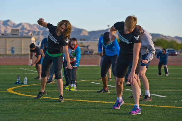 """Missy Cornish, wife of Col. Barry Cornish, 99th Air Base Wing commander, leads a group during a Warrior Trained Fitness workout on the field behind the Warrior Fitness Center March 13, 2014, at Nellis Air Force Base, Nev. Warrior Trained Fitness is a high intensity interval training workout designed as a part of the """"Life of a Warrior"""" concept of living a healthier lifestyle. (U.S. Air Force photo by Senior Airman Christopher Tam)"""
