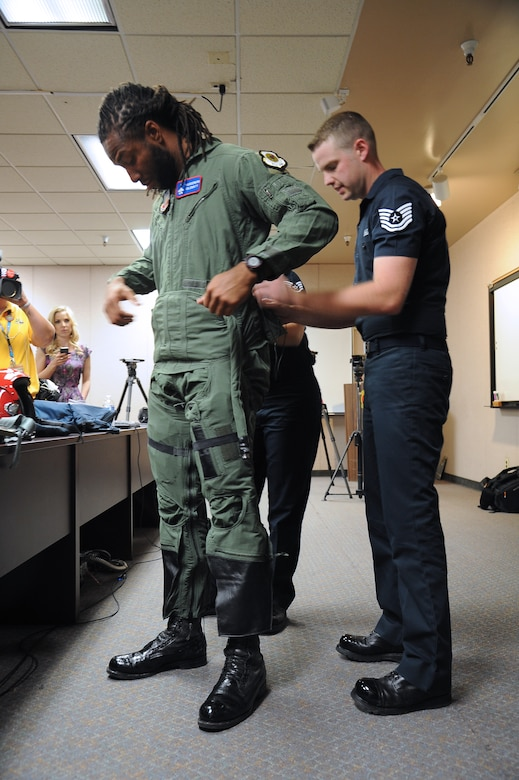 U.S. Air Force Thunderbirds crew members fit Larry Fitzgerald, Arizona Cardinals wide reciever, for a flight suit March 14. The Thunderbirds are scheduled to perform at approximately 3 p.m. on March 15 and 16 at Luke Air Force Base. (U,S, Air Force photo by Airman 1st Class Pedro Mota)