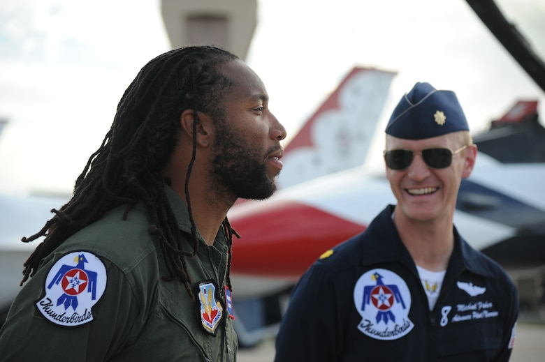 Larry Fitzgerald, Arizona Cardinals wide reciever, talks to Maj. Michael Fisher, U.S. Air Force Thunderbirds advance pilot/narrator, before taking a flight in a Thunderbird jet March 14. Fisher served as an F-16 instructor pilot and flight commander for the 310th Fighter Squadron at Luke Air Force Base. (U.S. Air Force photo by Airman 1st Class Pedro Mota)