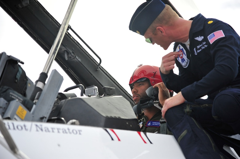 Larry Fitzgerald, Arizona Cardinals wide reciever, recieves final preflight instructions March 14 from Maj. Michael Fisher, U.S. Air Force Thunderbirds advance pilot/narrator, at Luke Air Force Base. Fisher piloted the jet that Fitzgerald flew in. (U.S. Air Force photo by Senior Airman Grace Lee)
