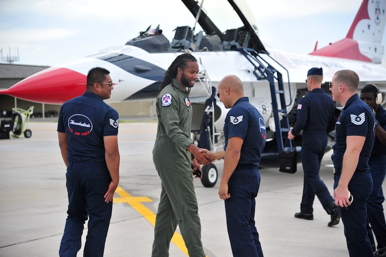 Larry Fitzgerald, Arizona Cardinals wide reciever, is greeted by members of the U.S. Air Force Thunderbirds March 13 as he makes his way to the jet he will be flown in at Luke Air Force Base, Ariz. The Thunderbirds are scheduled to perform at approximately 3 p.m. on March 15 and 16 at Luke's Open House and Air Show. (U.S. Air Force photo by Senior Airman Grace Lee)