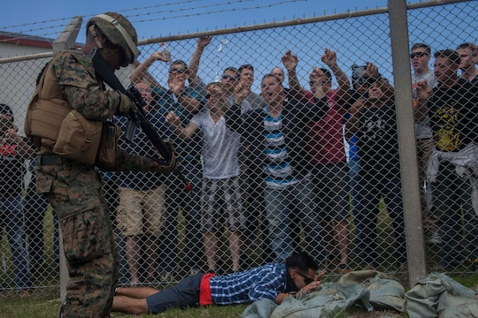 Lance Jadrieo T. Gant, a field artillery cannoneer with Battery G., Battalion Landing Team 2nd Battalion, 5th Marine Regiment, 31st Marine Expeditionary Unit, and a native of Baltimore, Md., detains a protester inside the perimeter of an American embassy during a mock hostile protest, March 15. The simulated embassy is home to the 31st MEU's Forward Command Element, a command cell that coordinates with a host nation's government to organize the delivery of humanitarian assistance and disaster relief supplies to people in need. The HA/DR training is in support of the 31st MEU's Certification Exercise, a training package that tests the capabilities of the MEU in a variety of scenarios and is evaluated by members of the Special Operations Training Group, III Marine Expeditionary Force.