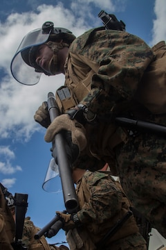 Lance Jadrieo T. Gant, a field artillery cannoneer with Battery G., Battalion Landing Team 2nd Battalion, 5th Marine Regiment, 31st Marine Expeditionary Unit, and a native of Baltimore, Md., prepares his riot shotgun for possible use during a mock hostile protest, March 15. The simulated embassy is home to the 31st MEU's Forward Command Element, a command cell that coordinates with a host nation's government to organize the delivery of humanitarian assistance and disaster relief supplies to people in need. The HA/DR training is in support of the 31st MEU's Certification Exercise, a training package that tests the capabilities of the MEU in a variety of scenarios and is evaluated by members of the Special Operations Training Group, III Marine Expeditionary Force.