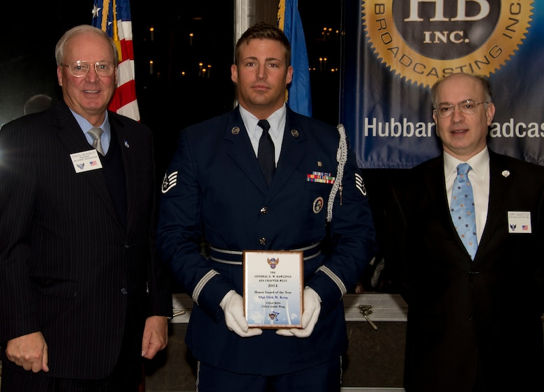 Staff Sgt. Dirk Krog, 210th Engineering Installation Squadron, receives an award from Retired U.S. Air Force Gen. Craig McKinley, President of the Air Force Association, and Larry Sagstetter, Rawlings Chapter President in St. Paul, Minn., Mar. 15, 2014. Krog is being honored for being the 133rd Airlift Wing Honor Guard of the Year during the Air Force Association's Annual Awards Dinner. 