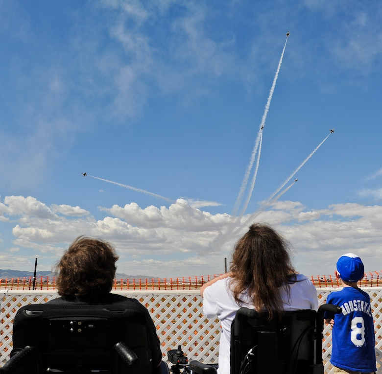 Kevin (left) and Tom Groeger watch the U.S. Air Force Air Demonstration Squadron Thunderbirds perform the delta burst during their practice performance Mar. 14 at Luke Air Force Base. The Groeger brothers both suffer from muscular dystrophy, which has progressively gotten worse. Both boys have lost the ability to walk due to the disorder weakening their muscles. (U.S. Air Force Photo by Staff Sgt. Darlene Seltmann)