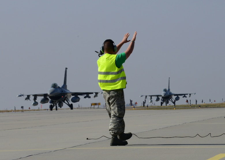 A 31st Aircraft Maintenance Squadron crew chief guides 555th F-16 Fighting Falcons into place, March 14, 2014, at Lask Air Base, Poland. A total of twelve 555th Fighter Squadron F-16 Fighting Falcons and 200 military personnel arrived to augment an off-site training event, which demonstrates an enduring partnership with NATO allies. (U.S. Air Force photo/Airman 1st Class Ryan Conroy)
