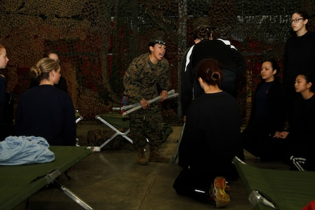 Sgt. Britni M. Garcia Green, a Platoon 4017, Company N, 4th Recruit Training Battalion, Marine Corps Recruit Depot Parris Island drill instructor, speaks with volume and intensity as she instructs poolees on how to properly break down a sleeping cot during Recruiting Station Kansas City's all-female pool function at  9th Marine Corps District Headquarters' Building 712 March 15, 2014. The purpose of the pool function was to give poolees their first glimpse of what to expect during recruit training.
