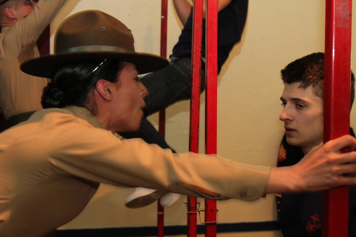 Sgt. Britni Garcia-Green, a drill instructor with 4th Recruit Training Battalion in Parris Island, S.C., instructs a poolee to mount the pull up bar at RS Kansas City's family night March 11. Garcia-Green is one of the first Marines the female poolees will meet when they arrive for training at the Marine Corps' only recruiting depot for females, at Parris Island.