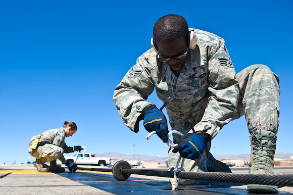 U.S. Air Force Senior Airman Demarcus Oliver, 99th Civil Engineer Squadron firefighter, inspects and ties rope around a BAK-12 aircraft arresting barrier on the flightline March 12, 2014, at Nellis Air Force Base, Nev. Rope is used to keep the barrier in place for aircraft landings. (U.S. Air Force photo by Senior Airman Christopher Tam)