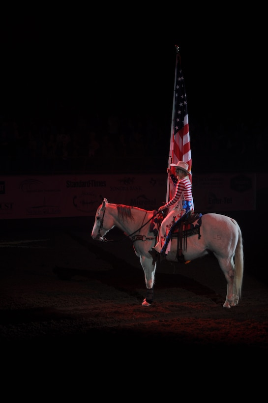 SAN ANGELO, Texas – Marissa Griffin, San Angelo Stock Show and Rodeo Drill Team ambassador, presents the American Flag at the beginning of the San Angelo Stock Show and Rodeo's Military Appreciation Night at the Foster Communication Coliseum here Feb. 26. Goodfellow Air Force Base's  Patriotic Blue sang the national anthem during the flag presentation. (U.S. Air Force photo/ Airman 1st Class Breonna Veal)