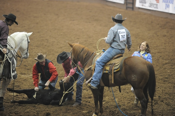 SAN ANGELO, Texas -- Col. Kimberlee Joos, 17th Training Wing Commander, hands the tie-down rope, or piggin' string, back to Jesse Clark, San Angelo Stock Show and Rodeo competitor, during the San Angelo Stock Show and Rodeo's Military Appreciation Night at the Foster Communication Coliseum here Feb. 26. The San Angelo Stock Show and Rodeo Drill Team Ambassadors presented the American and service flags during the night to honor all who serve or have served. (U.S. Air Force photo/ Staff Sgt. Laura R. McFarlane)