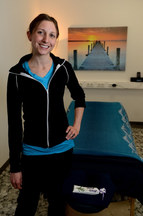 Andrea Trebesh, a massage therapist from Colorado Springs, Colo., stands in front of her massage table at Spangdahlem Air Base, Germany, March 14, 2014. Trebesh is a licensed therapist who applies her knowledge of sports and physical activity to help determine which muscles need attention. (U.S. Air Force photo by Airman 1st Class Kyle Gese/Released)