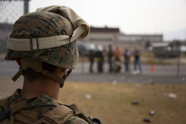 A Marine with the 31st Marine Expeditionary Force keeps protesters at bay during a noncombatant evacuation operation aboard Marine Corps Air Station Iwakuni, Japan, March 19, 2014. The Osprey aircraft allows the MEU to reach greater distances at a faster speed than ever before.