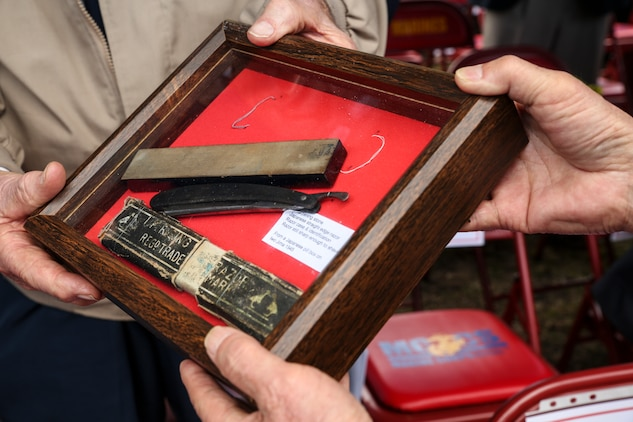 Prior to the opening ceremony, Owen Agenbroad, a Marine veteran and combat message runner during the Battle of Iwo Jima, presents a shadow box to Yoshikau Higuichi March 19 during the annual Reunion of Honor ceremony. The shadow box contained a sharpening stone, Japanese straight-edge razor, razor case, tin cup and identification tags. Agenbroad found these items in a destroyed gun emplacement during the battle and wanted to return them to Higuichi, the son of the fallen Japanese solider they originally belonged to. (U.S. Marine Corps photo by Cpl. Jose D. Lujano/Released)
