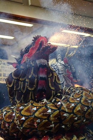 A member of the Fire Snake Theater, clad in a dragon costume, uses fireworks to portray the beast's fire-breathing effect during the Kagura performance inside of the Matthew C. Perry High School cafeteria as part of the Japanese American Society Culture Festival, March 8, 2014 aboard, Marine Corps Air Station Iwakuni, Japan. Performers depicted the mythological tale of Yamata-no-Orochi, an eight-headed and eight-tailed serpent.
