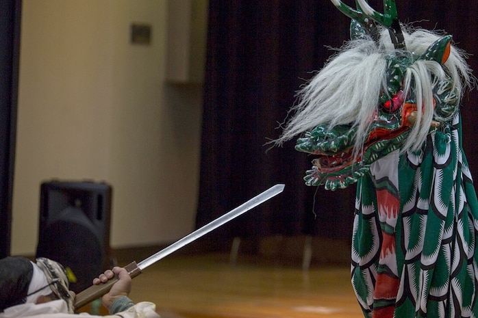 A member of the Fire Dragon Theater, clad in a dragon costume, uses fireworks to portray the beast's fire-breathing effect during the Kagura performance inside of the Matthew C. Perry High School cafeteria as part of the Japanese American Society Culture Festival, March 8, 2014 aboard, Marine Corps Air Station Iwakuni, Japan. Performers depicted the mythological tale of Yamata-no-Orochi, an eight-headed and eight-tailed serpent.
