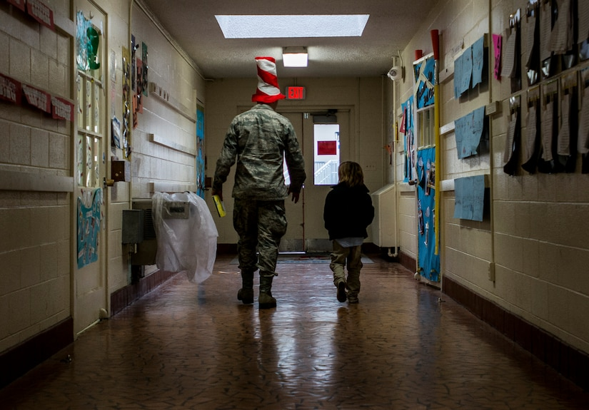 Airman 1st Class Max Wanzy, 628th Contracting Squadron specialist, walks down the hall with a student from St. Andrews Elementary School March 7, 2014. More than 30 Airmen from Joint Base Charleston attended the event having breakfast with the children, answering question about the Air Force and reading the children's favorite Dr. Seuss book. (U.S. Air Force photo/ Senior Airman Dennis Sloan)