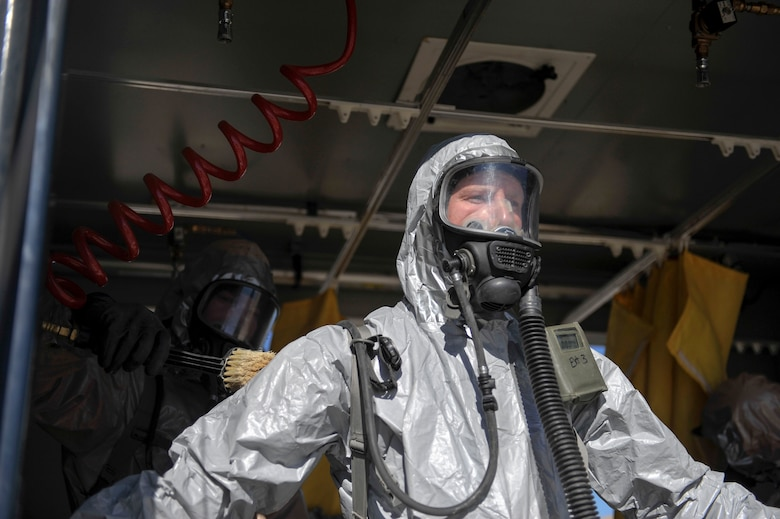 Colorado National Guard Chemical, Biological, Radiological, Nuclear and High-Yield Explosive Enhanced Response Force Package search and rescue team member stands in the decontamination tent to be cleaned during an exercise March 8, 2014, in Lakewood, Colo. The CERFP team spends one weekend every three months training in an emergency exercise to refine their skills in search and rescue, decontamination and medical procedures. (U.S Air Force photo by Airman 1st Class Samantha Saulsbury/Released)