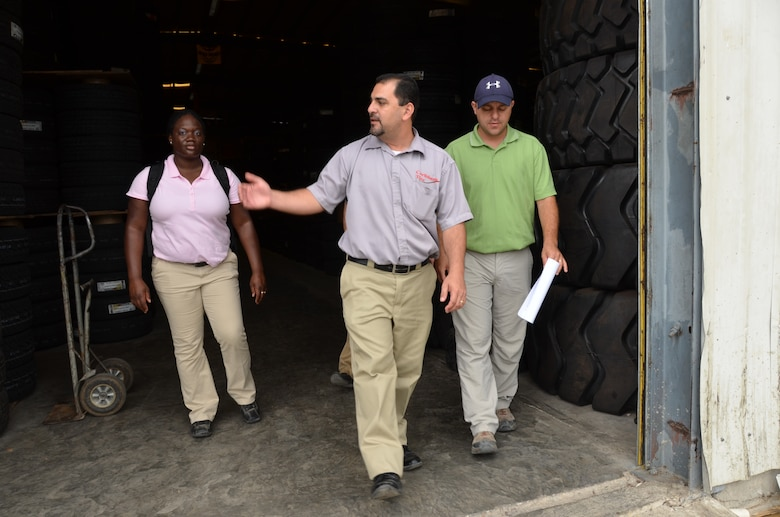 Staff Sgt. Marcedes Fleming (left), New Horizons pay agent, and Tech. Sgt. Ryan Schnepf (right), New Horizons contracting officer, take a tour of a local tire repair shop after coming to a purchase account agreement March 13. Contracting officials will be working with several local businesses throughout the exercise. (U.S. Air Force photo by Master Sgt. Kelly Ogden/Released)