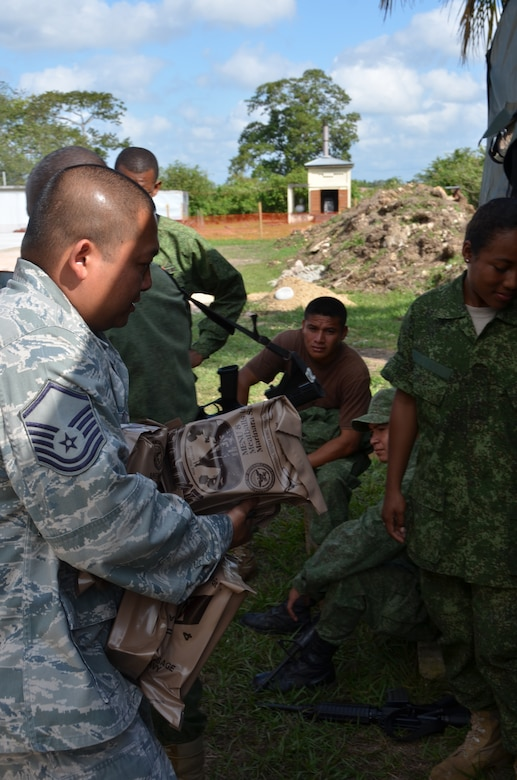 Master Sgt. Enrique Naranjo, New Horizons logistics superintendent, hands out MREs and water to the Belize Defence Force soldiers securing New Horizons equipment at the Belmopan Hospital construction site, March 11. During the past 20 years, U.S. Southern Command has worked side-by-side with the Belize Defence Force as well as the Ministries of Health and Education to conduct combined exercises to strengthen each participant's response to humanitarian relief scenarios. (USAF photo by Master Sgt. Kelly Ogden/Released)