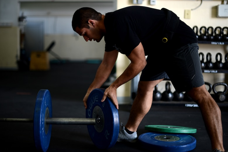 U.S. Air Force Senior Airman Anthony Pelaez, 52nd Component Maintenance Squadron jet engine mechanic from Miami, loads a 45-pound weight to a barbell at Spangdahlem Air Base, Germany, March 14, 2014. Comprehensive Airmen fitness is made up of four categories: physical, mental, emotional and spiritual fitness. (U.S. Air Force photo by Airman 1st Class Kyle Gese/Released)