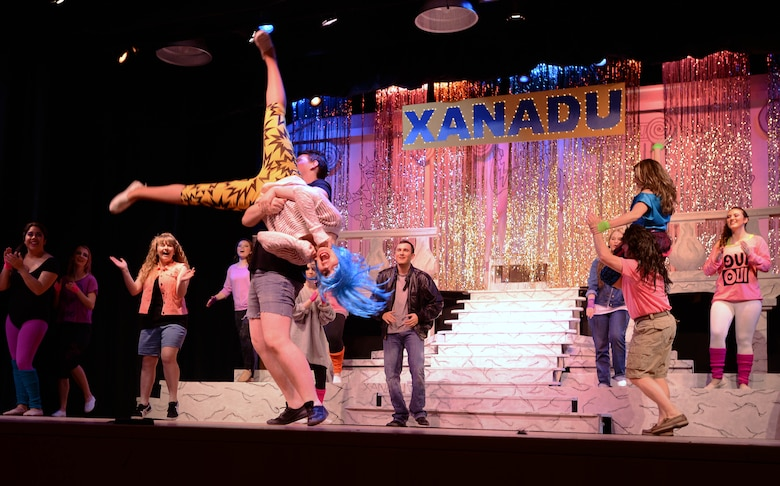 """Members of the cast dance for their last act during the Aviano Community Theater dinner theater performance of """"Xanadu,"""" March 15, 2014, at Aviano Air Base, Italy. """"Xanadu"""" is an '80s love story between an uninspired artist and a Greek muse who helps him fulfill a lifelong dream of opening a roller disco. (U.S. Air Force photo/Airman 1st Class Deana Heitzman)"""