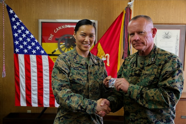 Major Gen. Lawrence Nicholson, commanding general of 1st Marine Division, congratulates 1st Lt. Thuymi Dinh, communications officer, 1st Battalion, 11th Marine Regiment on earning the Camp Pendleton female athlete of the year award at Marine Corps Base Camp Pendleton, Calif., Feb. 10, 2014. Dinh, a native of Anaheim, Calif., has participated in numerous triathlons and says she hopes to one day complete an ironman triathlon. Dinh also was a runner up in the Marine Corps female athlete of the year award. She will deploy to Afghanistan in support of Operation Enduring Freedom later this year.