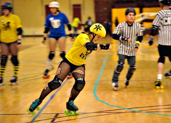 Risky Bizness, also known as Senior Airman Lindsey Rath, 36th Fighter Squadron operations intelligence analyst, turns a corner during a roller derby bout at U.S. Army Garrison Humphreys, Republic of Korea, March 8, 2014. Rath is one of several active duty military members that make up the KimChicks roller derby team. (U.S. Air Force photo/Senior Airman Siuta B. Ika)