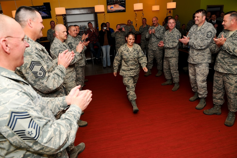 Master Sgt. Christina Duran, Air Reserve Personnel Center, walks through a gauntlet at the Team Buckley Senior Master Sergeant Release Party March 20, 2014, at Panther's Den on Buckley Air Force Base, Colo. Duran was one of five senior master sergeant selects for Team Buckley and one of 999 selects for the Air Force. (U.S. Air Force photo by Senior Airman Phillip Houk/Released)