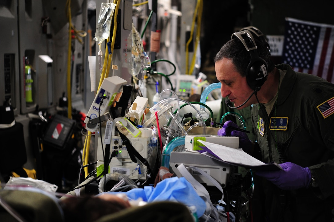 Lt. Col. Richard Lorraine cares for an intensive care patient during a flight back to Joint Base Andrews, Md., Dec. 19, 2013. Lorraine, a member of a Critical Care Air Transport Team belongs to the 111th Medical Group. (U.S. Air Force photo/Airman 1st Class Aaron Stout)