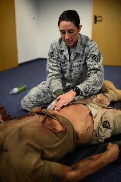U.S. Air Force Staff Sgt. Elizabeth Butler, 52nd Medical Operations Squadron aerospace medical technician from Tampa, Fla., assesses a mock patient's abdomen during a readiness skills verification training class March 19, 2014 at Spangdahlem Air Base, Germany. Technicians learn to check the abdomen for any signs of internal trauma to determine the level of response required. (U.S. Air Force photo by Senior Airman Gustavo Castillo/Released)