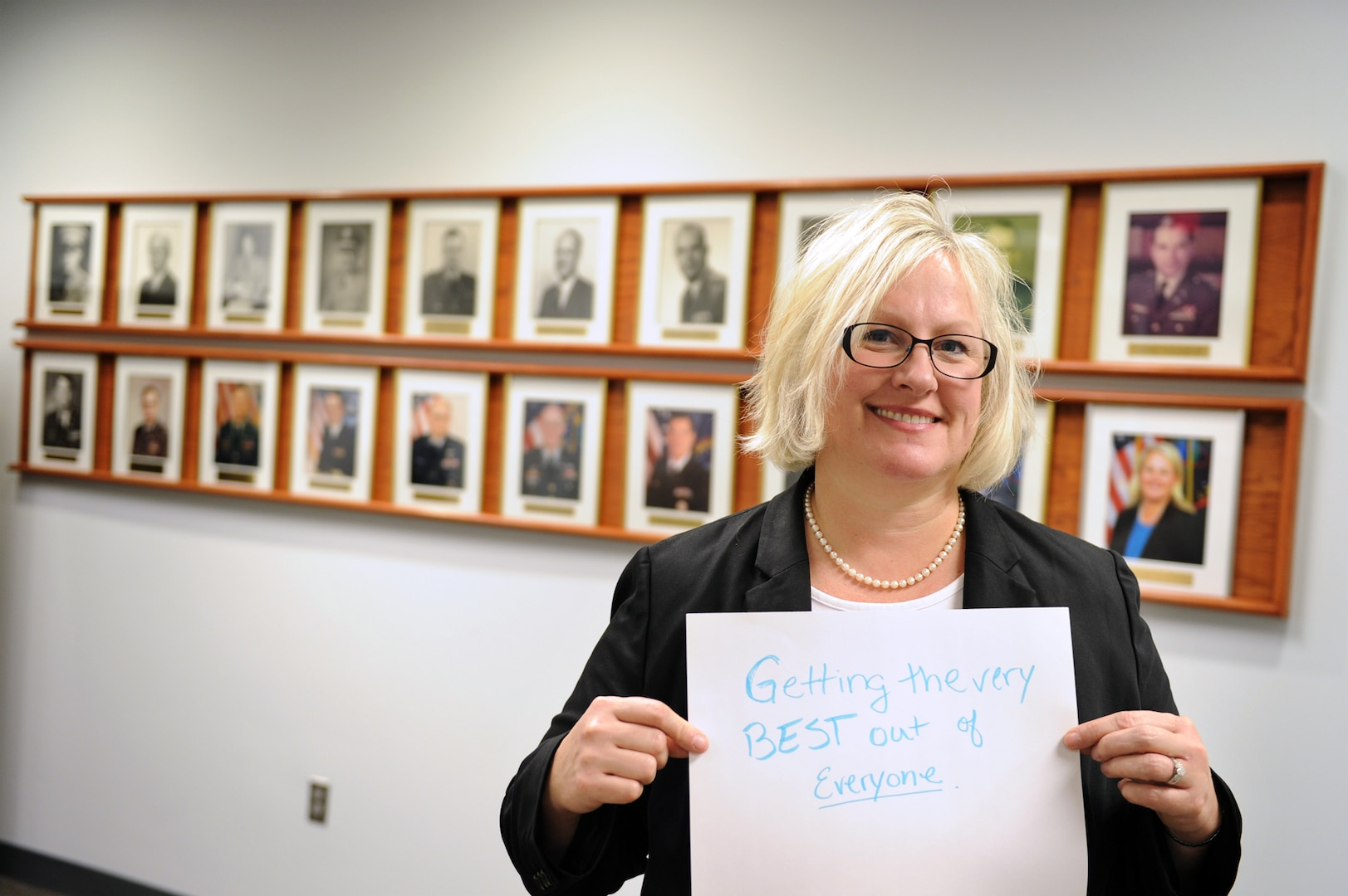 """Dr. Kathryn Morici, new director of DIA's National Center for Medical Intelligence, showcases her answer to the question """"What does Women's History Month mean to you?"""" She is standing in front of the wall highlighting center directors, of which she is the first female and second civilian."""